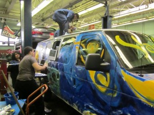 Bassick Students painting van for use in Monster Truck Show at the Arena